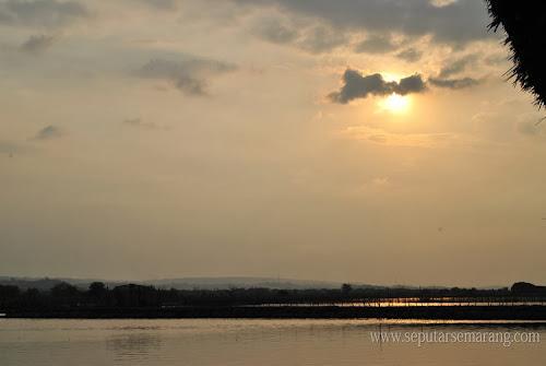 matahari terbenam di tanjung laut