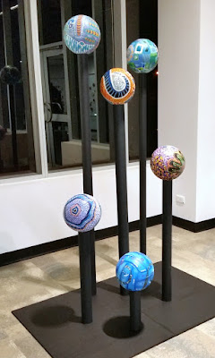 Six volleyballs are decorated with painted designs. They are displayed at different heights atop straight black vertical poles which are mounted on a black flat rectangular base.