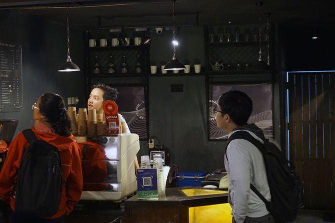 Pengunjung dan barista di depan meja bar