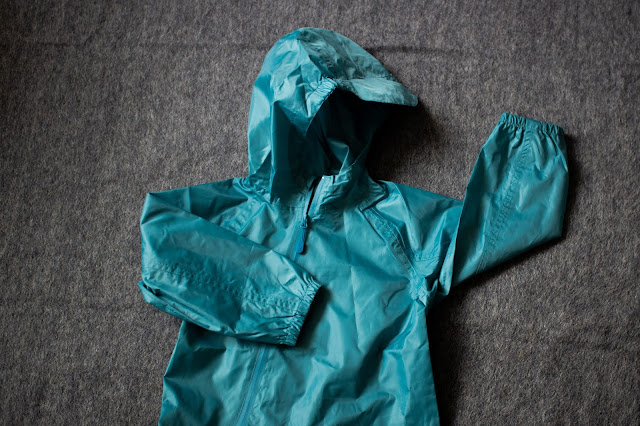 A photo of the top half of the Ocean teal coloured puddlesuit in age 3 to 4 with a hood and elasticated arms