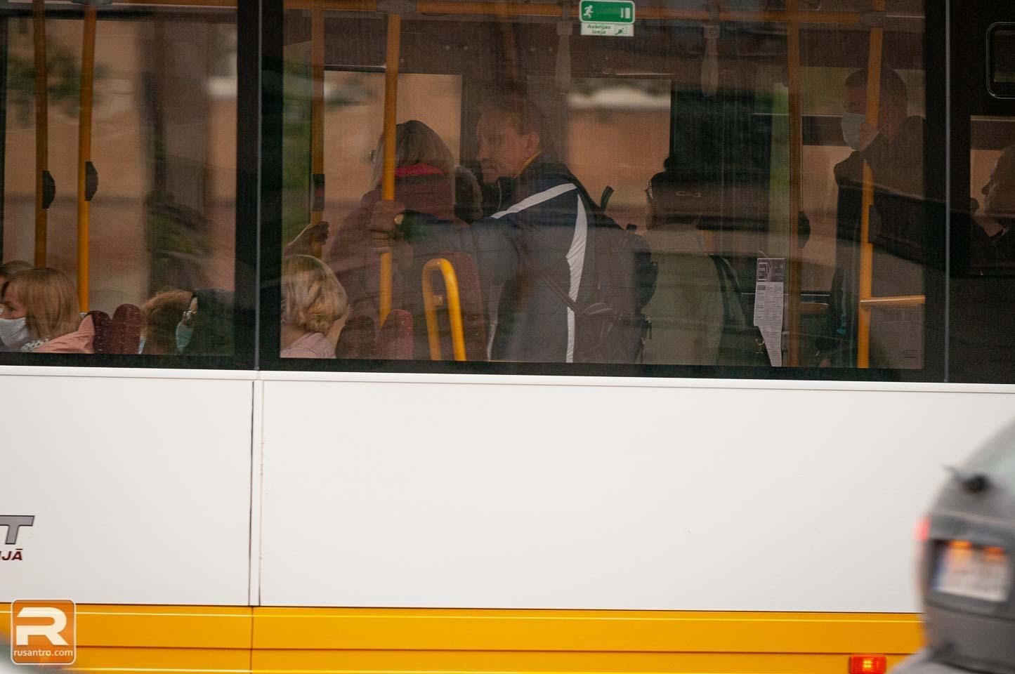 Cilvēki autobusā ar sejas maskām