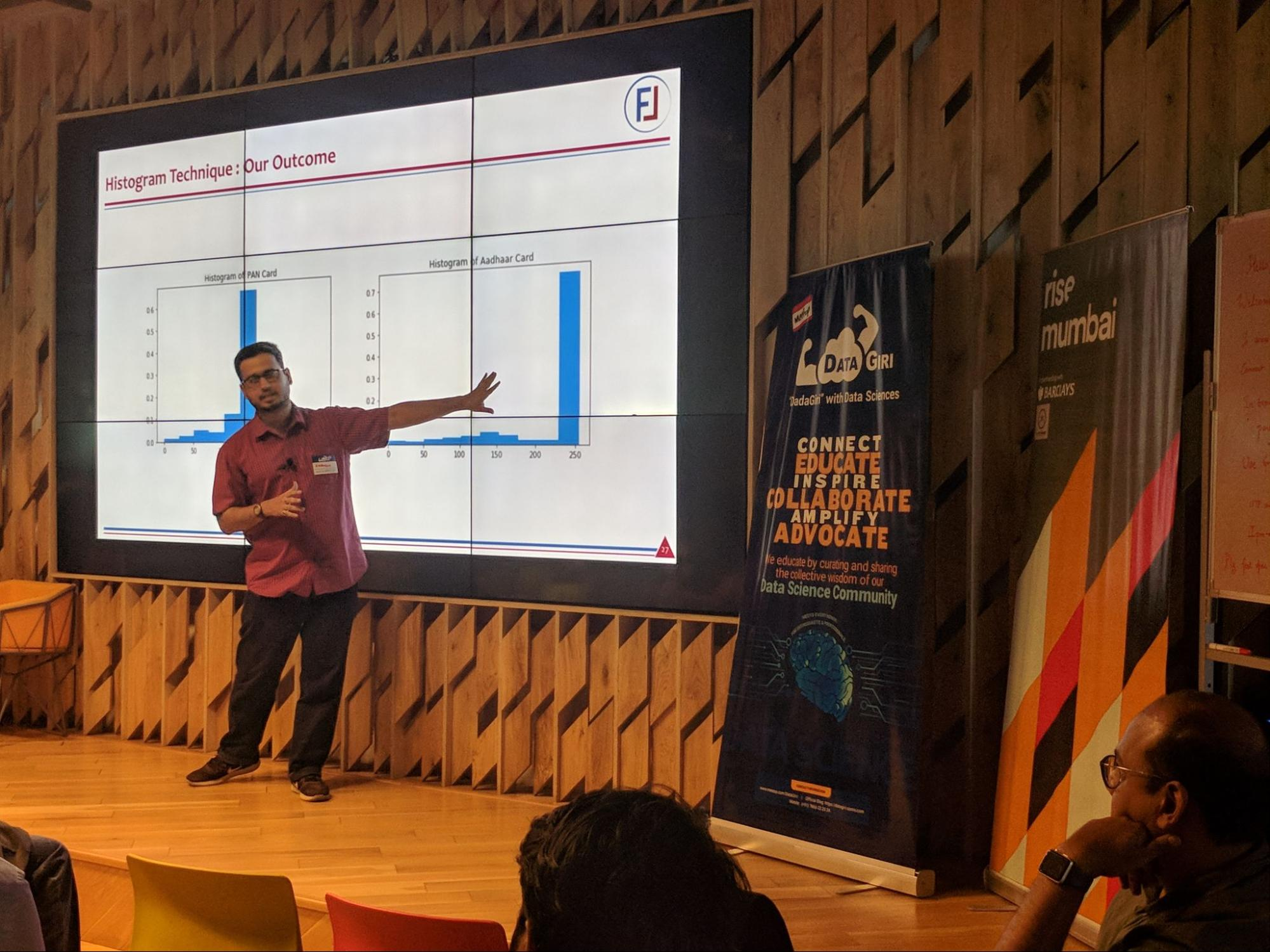 Image shows Bhavesh Bhatt onstage giving a presentation
