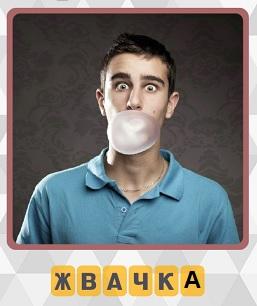 мужчина надул во рту жвачку в виде пузыря
