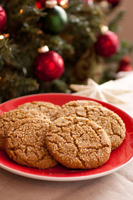A red plate with a pile of ginger cookies on it