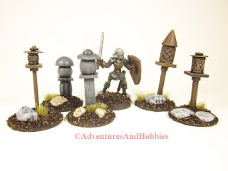 A miniature fantasy knight wanders through a group of 25-28mm scale shrines.