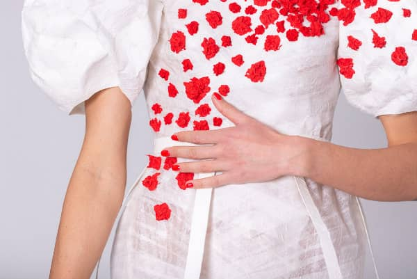 detail of paper dress bodice with scattered red ornaments and puffed sleeves