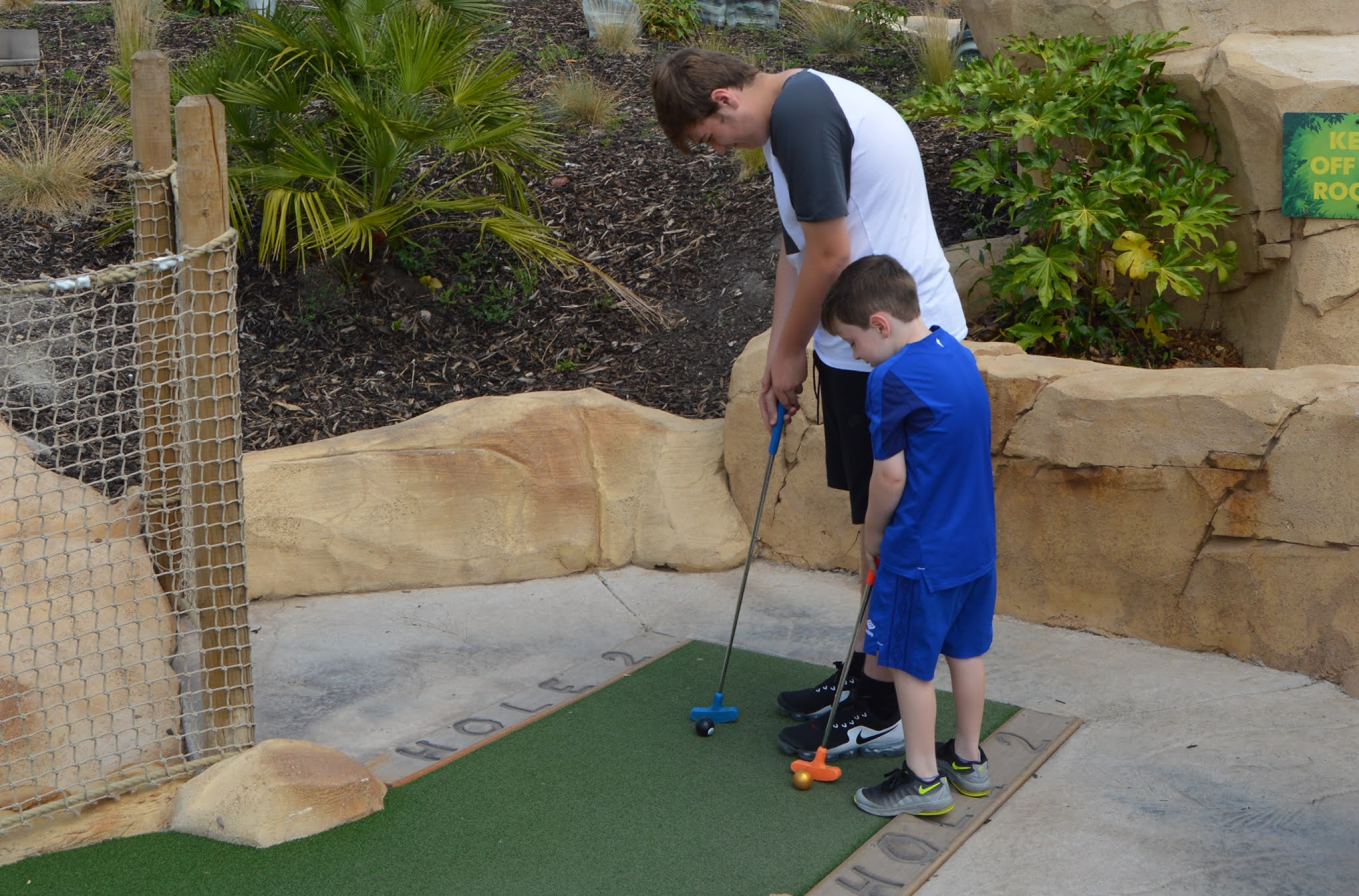 boys playing mini golf