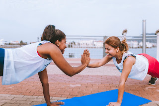 Two ladies touch their hands while they exercise