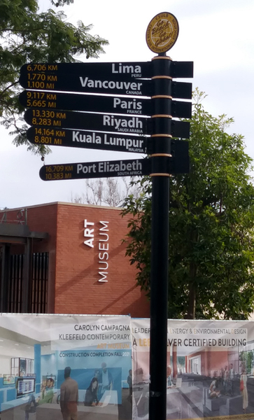 This sign shows the distances to six different cities around the world from this location on the CSULB campus.