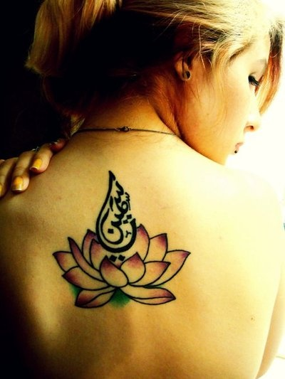 chica de espaldas con tatuaje de flor del loto en la espalda