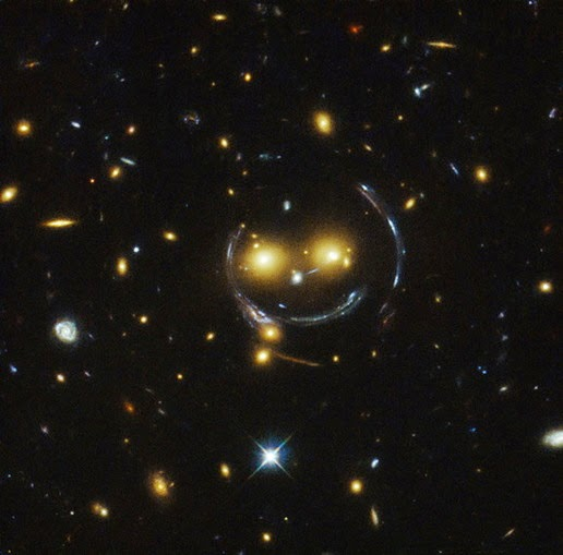 Image of SDSS J1038 + galaxy cluster 4849 is seen smiling .. In fact, the gravitational lens create indentations smile and face it.