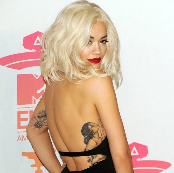 Rita Ora posando de tres cuartos, lleva pelo rubio platino, vemos su tatuaje en las costillas, un tatuaje de estilo old school