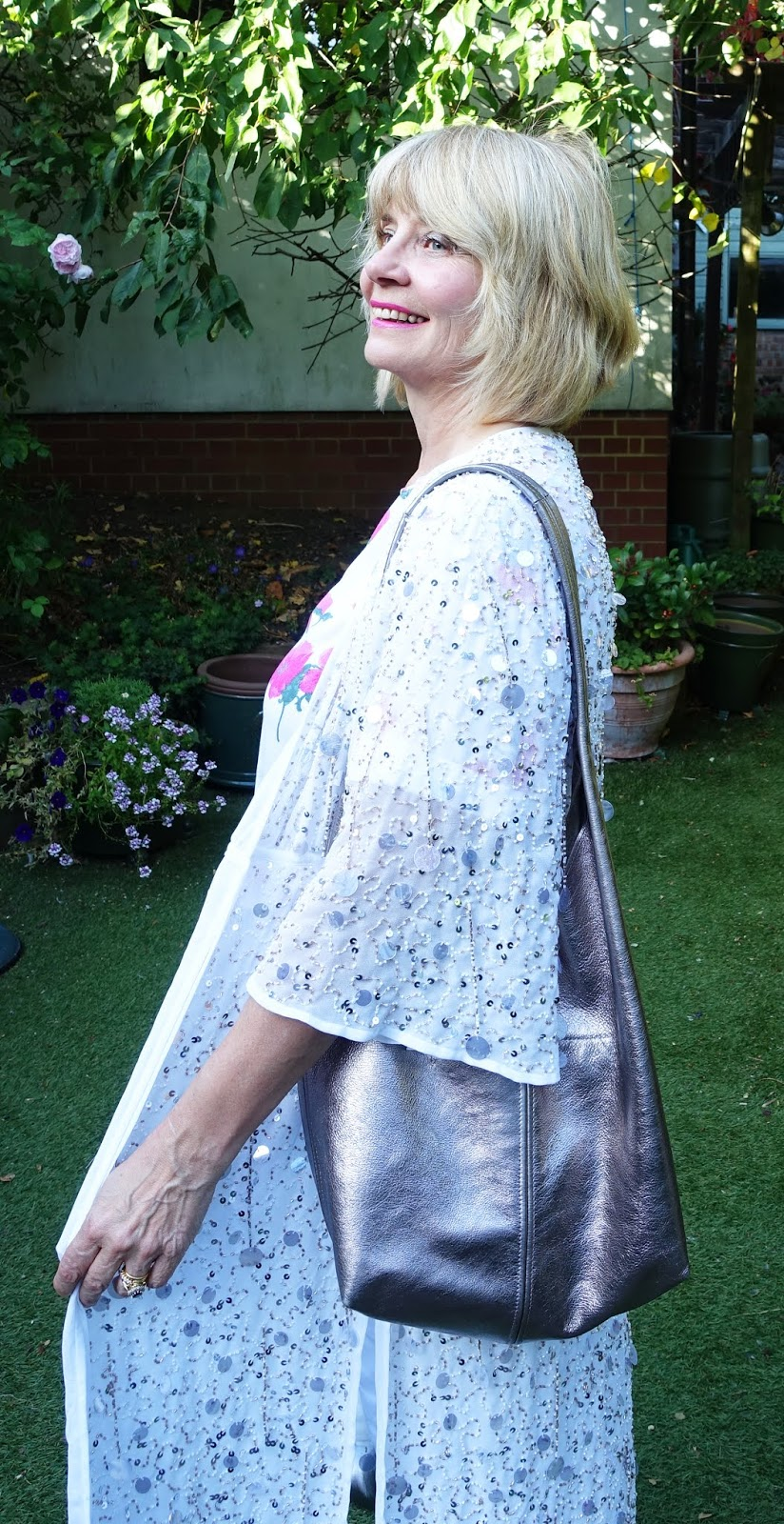 Style blogger Gail Hanlon from Is This Mutton in a white embellished coatigan from River Island, white flared jeans and a floral patterned top.