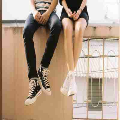 gf and bf sitting on a wall together