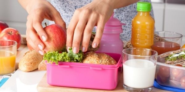 closeup of mum packing an apple into a full pink lunch box