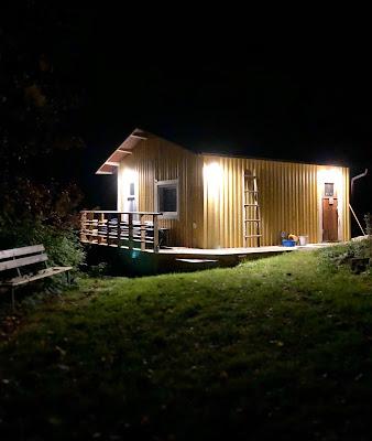 Keltainen sauna kylpee valossa keskellä pimeyttä