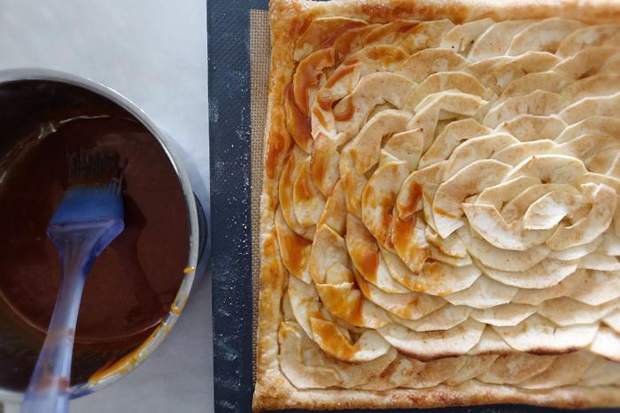 brushing partially baked tart with caramel