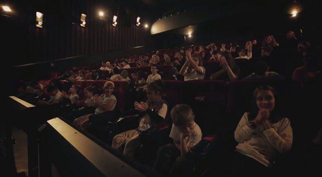 Cinemagine: sala de cinema às escuras, várias pessoas sentadas