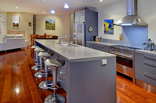 Photo of modern kitchen and kitchen island with bar chairs