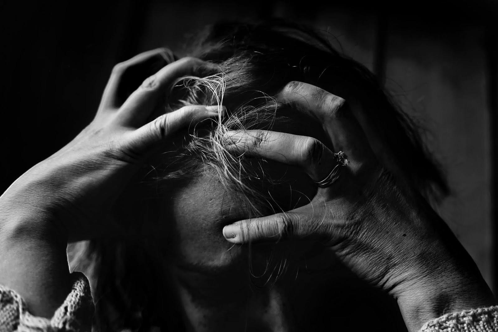 photo en noir et blanc d'une personne qui se tient la tête en signe de souffrance