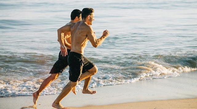 Homens a correr na praia
