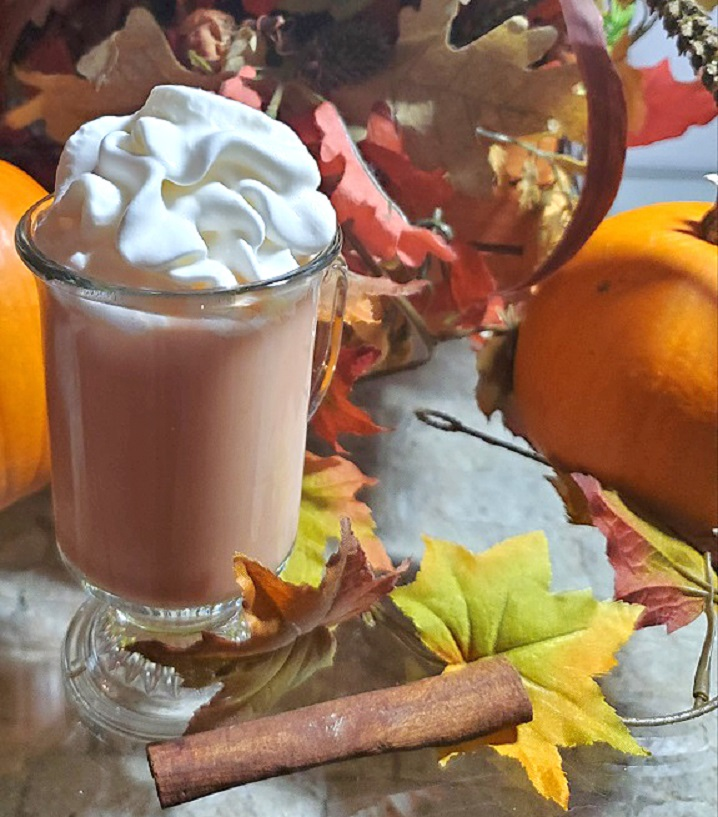 this is a cup of pumpkin spice latte in a glass cup with whipped cream with a cinnamon stick and fall foliage in the background along with a sugar pie pumpkin