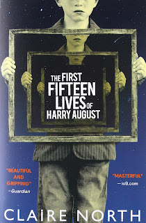 "A white teenage boy holds up a frame which holds the image of himself holding the frame, with one more recursion of himself. The innermost frame contains the words ""The First Fifteen Lives of Harry August"""