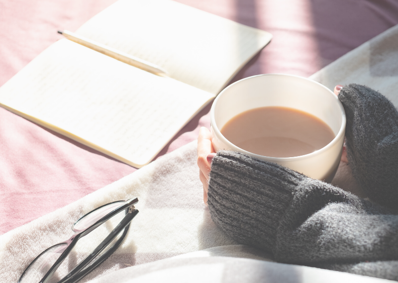 A lady with a cup of coffee and a journal in a post about how to start journaling and make it a habit