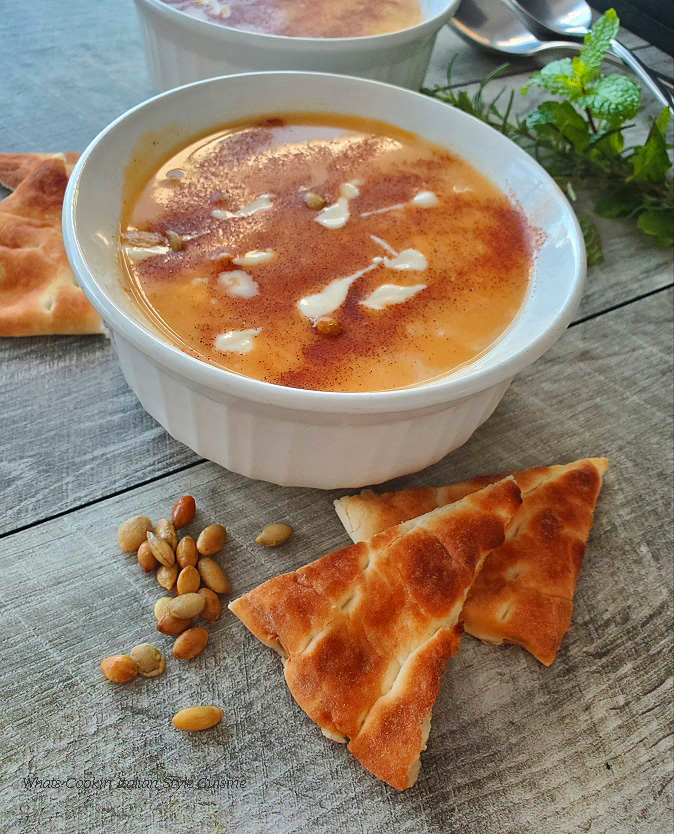 this is a bowl of butternut squash soup swirled with cream topped with pumpkin seeds pepitas, and served with pita bread