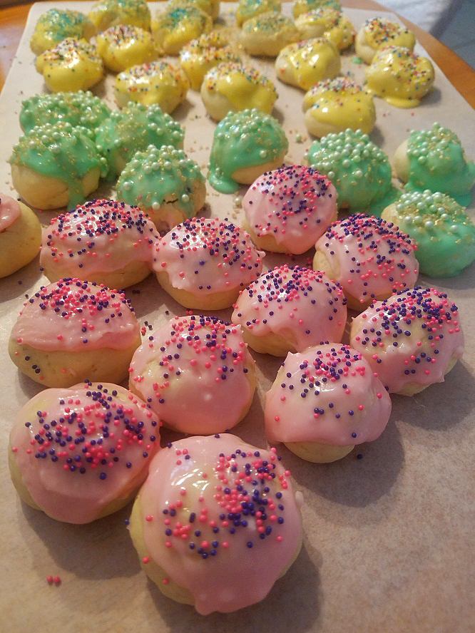 these are pink green and yellow frosted cookies for Easter with sprinkles on top