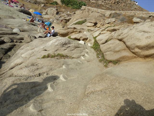 Na skałach nad brzegiem greckiego morza pod niebieskimi parasolami wypoczywają turyści odziani w stroje kąpielowe