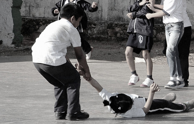 Menino batendo colega menina na escola; plano de aula sobre bullying