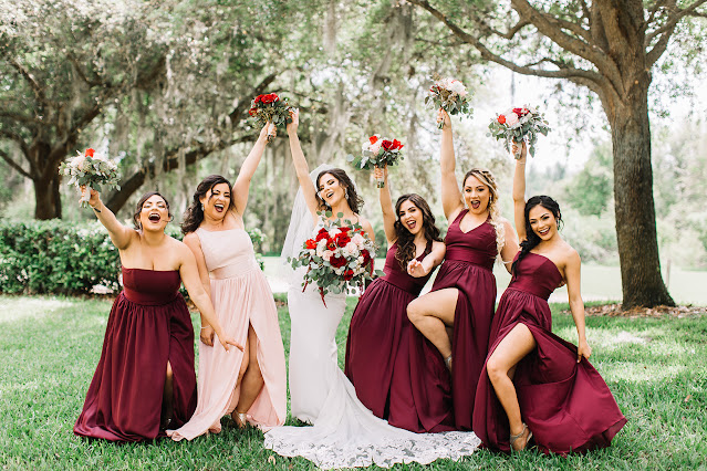 bride and bridesmaids in burgundy dresses taking photos