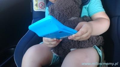 dziecko siedzi w foteliku z misiem
