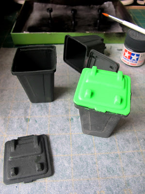 Three modern dolls' house miniature wheelie bins, on a workbench after being painted.