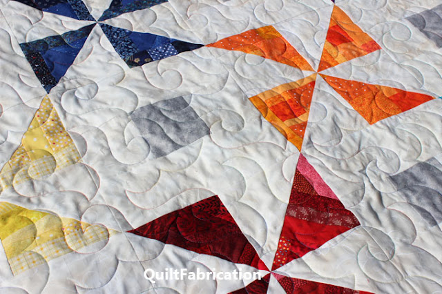 quilting with multicolored thread on a pinwheel quilt