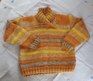 A knitted sweater in orange and yellow rainbow stripes. Long sleeves and a wrapped neck with a plain front