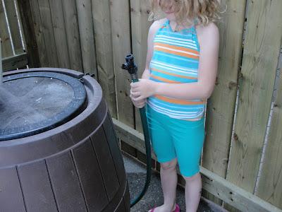child operating a rain barrel