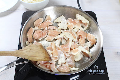 Raw chicken cooking in a skillet