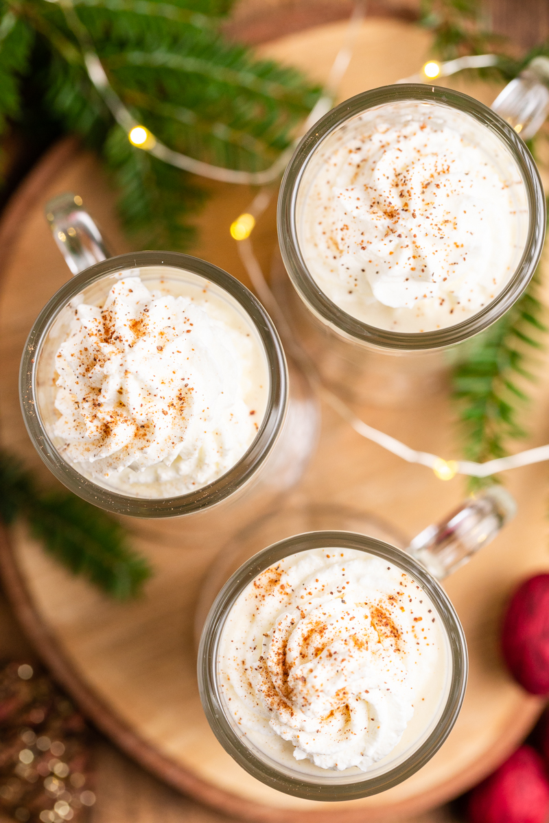 Overhead photo of 3 mugs of Keto Eggnog (Dairy-Free & Sugar-Free) on a round wooden cutting board.