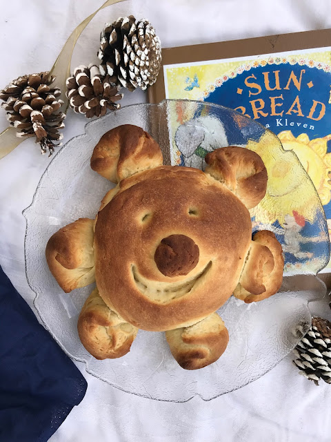 A baked loaf of sun bread on a platter next to a copy of the Sun Bread book.