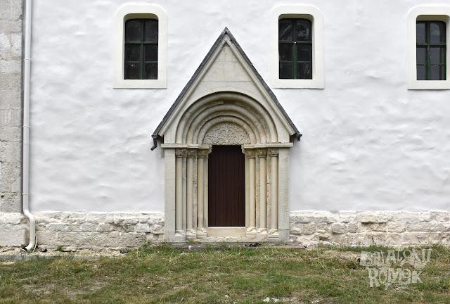 Románkori íves, bélletes templomkapu Monoszlón az ajtó felett félköríves, indás életfa motívummal.