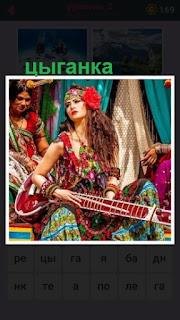 цыганка в разноцветной одежде играет на гитаре и поет