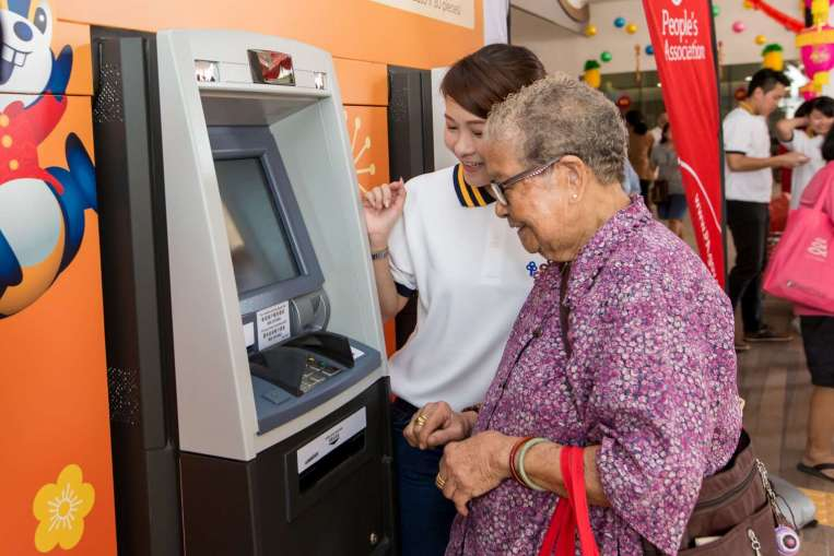People lining up to use the pop-up ATMs at Ci Yuan Community Club at Hougang Avenue 9. POSB ambassadors will be at all locations to help customers.
