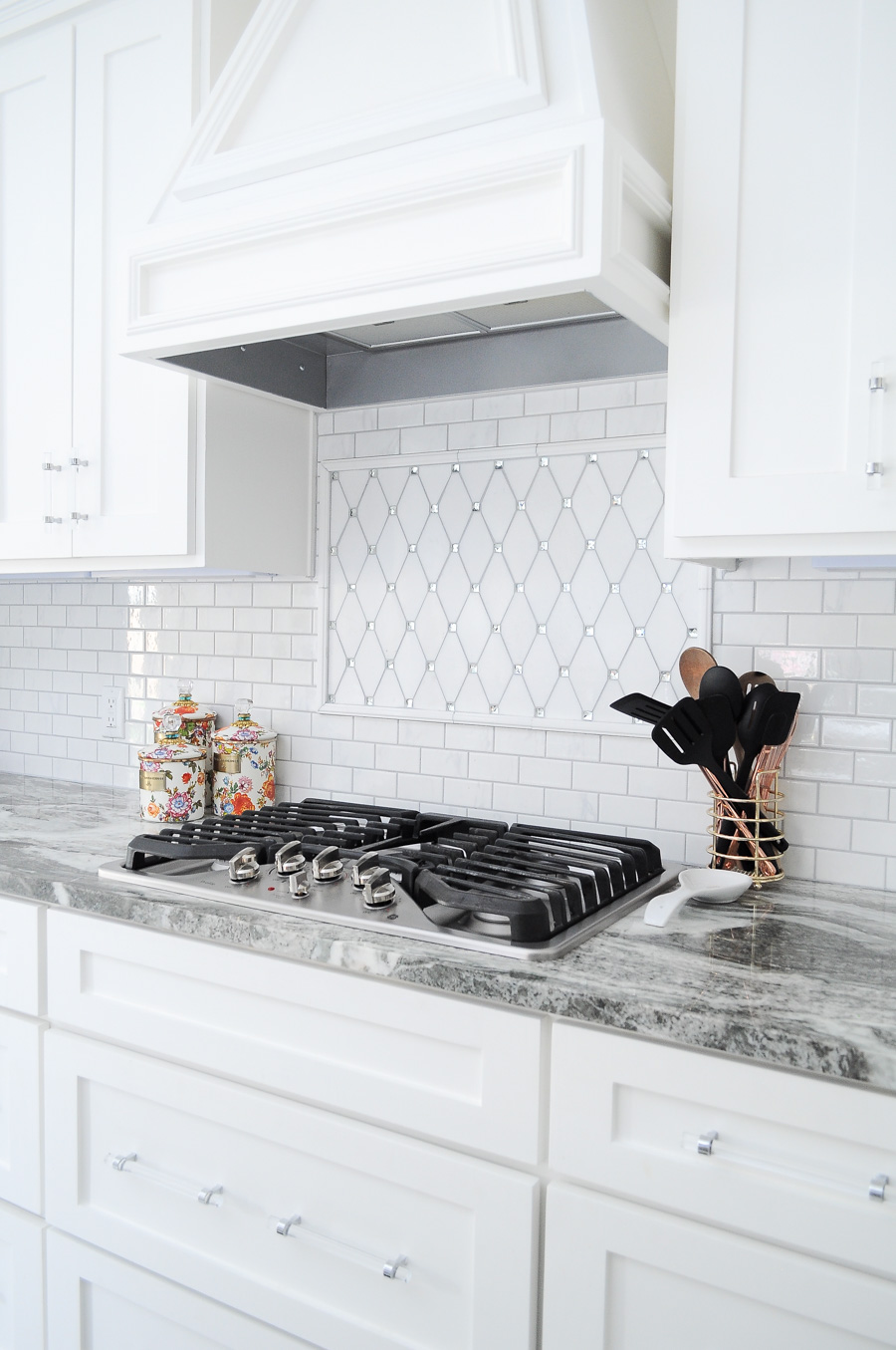 Tile Bar thassos tile paired with a marble subway backsplash, gray marbled counters, lucite drawer and cabinet pulls.