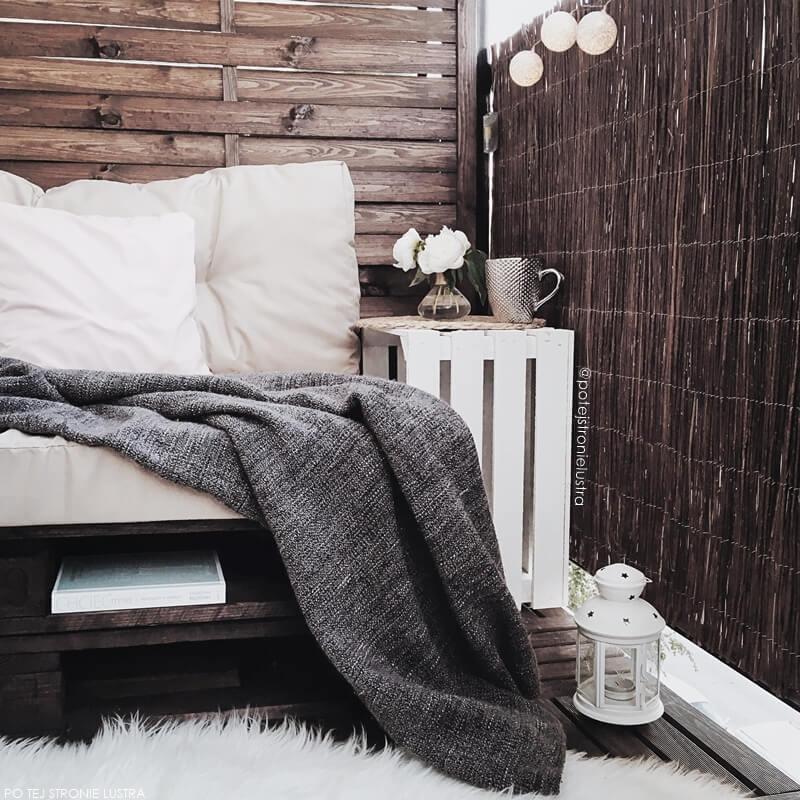 siedzisko z palet na balkonie w bloku i stolik z drewnianej białej skrzynki