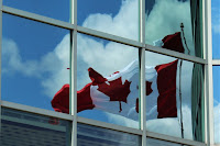 reflection of Canadian flag in a glass building