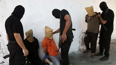 Hamas members prepare to execute Palestinians for allegedly spying for Israel in August 2014.