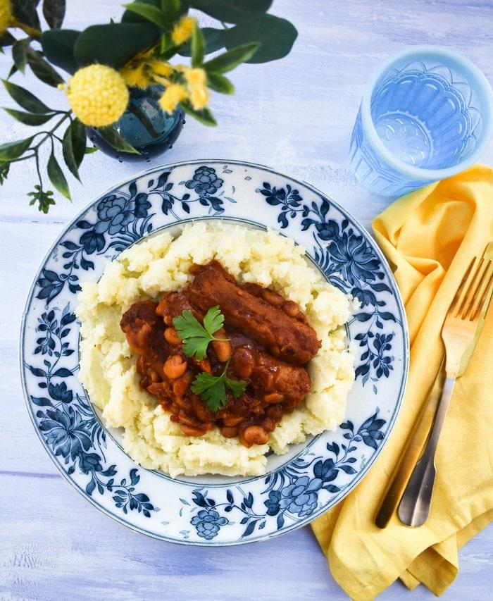 Vegan sausage stew on a bed of mashed potato