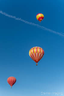 Cramer Imaging's fine art photograph of three colorful hot air balloons taking flight in Panguitch Utah with a blue morning sky with contrail